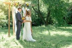 新娘和新郎在室外的婚礼期间 免版税库存照片