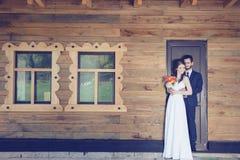 新娘和新郎在房子golding的togher前面 免版税库存照片