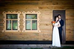 新娘和新郎在拿着togher的房子前面 库存图片