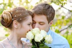 新娘和新郎在春天停放嗅到一朵白色玫瑰 免版税库存照片