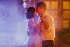 新娘和新郎在模糊的背景中的跳舞第一个舞蹈 免版税库存图片