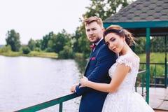 新娘和新郎在河岸的码头站立 免版税库存图片