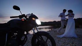 新娘和新郎在海滩在日落 他们在有光的摩托车附近摆在  拉丁文爱 影视素材