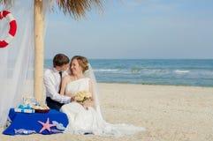 年轻新娘和新郎在海滩 免版税库存图片