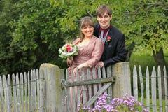 新娘和新郎在秋天在木花园大门 库存图片