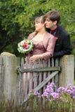 新娘和新郎在秋天在木花园大门 库存照片