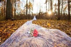 新娘和新郎在秋天森林里和在长的新娘面纱的新娘花束 免版税库存图片
