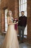 新娘和新郎在窗口和葡萄酒砖墙附近摆在 图库摄影