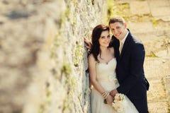 新娘和新郎在老被破坏的城堡墙壁附近 库存图片