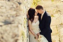 新娘和新郎在老被破坏的城堡墙壁附近 免版税库存图片