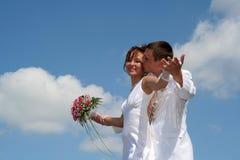 新娘和新郎在蓝天背景 免版税库存图片