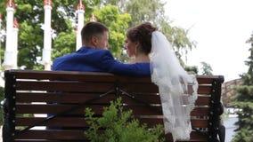 新娘和新郎在长凳的公园 影视素材