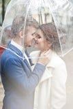 新娘和新郎在雨中,当微笑时 免版税库存图片