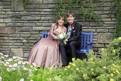 新娘和新郎坐蓝色长凳 免版税库存照片