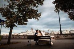 新娘和新郎坐长凳在河附近在老城市 除草在布达佩斯 图库摄影