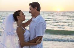 新娘和新郎已婚夫妇日落海滩婚礼 免版税库存照片