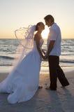 新娘和新郎已婚夫妇日落海滩婚礼 免版税库存图片