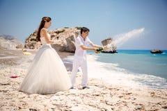新娘和新郎开放香槟在海滩地中海 免版税图库摄影