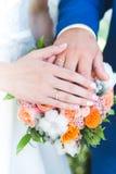 新娘和新郎手和圆环在婚礼花束 图库摄影