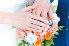 新娘和新郎手和圆环在婚礼花束 免版税图库摄影