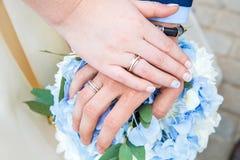 新娘和新郎手和圆环在婚礼花束 库存照片