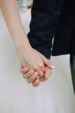 新娘和新郎握手,特写镜头,美丽的皮肤 免版税库存图片