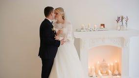 新娘和新郎摆在摄影师在演播室在壁炉附近用香槟 股票录像