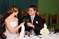新娘和新郎敬酒 免版税库存照片
