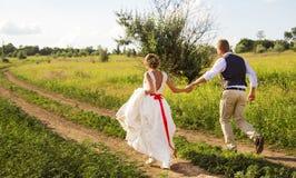 新娘和新郎沿道路愉快地跑在公园 新郎握新娘` s手 免版税库存图片