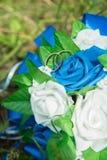 新娘和新郎的两只金戒指在花束手工制造 免版税库存照片