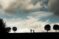 新娘和新郎的剪影在天际 库存照片