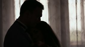 新娘和新郎的剪影在窗口前面的大厅里 愉快一起 的早晨准备 影视素材