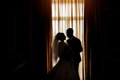 新娘和新郎的剪影在窗口wi的背景 库存图片