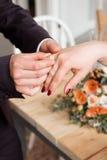 新娘和新郎的婚戒和手 在仪式的年轻婚礼夫妇 婚姻 爱的男人和妇女 两愉快的人c 库存图片