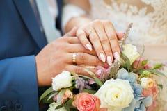 新娘和新郎的恋人的手 婚姻白色的背景明亮的环形 免版税库存图片