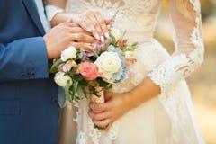 新娘和新郎的恋人的手 婚姻白色的背景明亮的环形 免版税库存照片