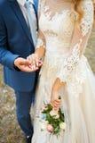 新娘和新郎的恋人的手 婚姻白色的背景明亮的环形 免版税图库摄影