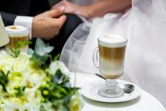 新娘和新郎的手一杯咖啡的 在桌的婚礼花束 免版税库存照片
