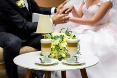 新娘和新郎的手一杯咖啡的 在桌的婚礼花束 库存照片