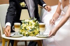 新娘和新郎的手一杯咖啡的 在桌的婚礼花束 免版税库存图片