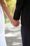 新娘和新郎的手与一个婚戒在街道上 库存图片