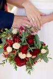 新娘和新郎的手与圆环在婚姻的花束 o 免版税库存照片