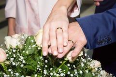 新娘和新郎的手与圆环在婚礼花束 婚姻概念 免版税图库摄影