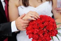新娘和新郎的手与圆环在婚礼花束 免版税库存图片