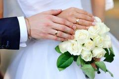 新娘和新郎的手与圆环在婚礼花束 库存照片