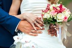 新娘和新郎的手与圆环握他们的手在一件礼服有花花束的  新娘概念礼服婚姻纵向的台阶 免版税库存照片