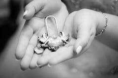 新娘和新郎的手与葡萄酒锁 库存图片