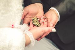 新娘和新郎的手与葡萄酒锁 免版税库存照片