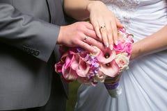 新娘和新郎的手在婚礼花束的 库存图片