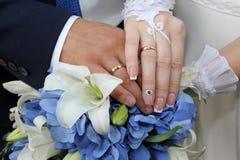 新娘和新郎的手在新娘花束 图库摄影